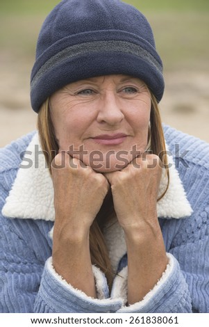 Portrait thoughtful attractive mature woman outdoor, wearing warm bonnet and wool jacket, resting relaxed chin on hands blurred green background. - stock photo
