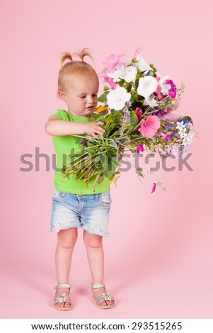 Portrait toddler girl with bouquet garden flowers on pink background - stock photo