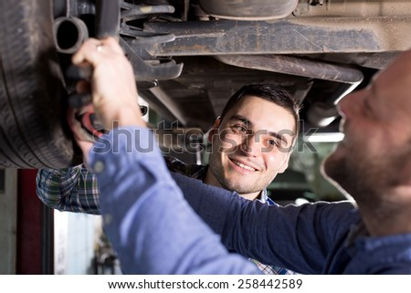 portrait two men in coveralls working at auto repair shop closeup. - stock photo