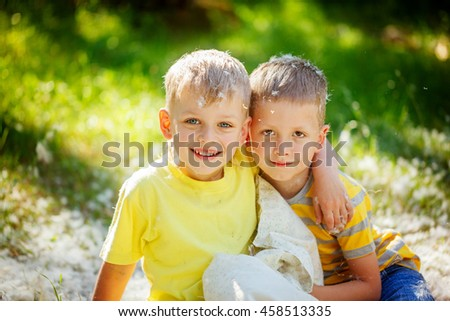 Portrait two smiling Kids having fun  outdoors. Two children relax in a sunny summer garden. Pillow fight. Friendship concept.