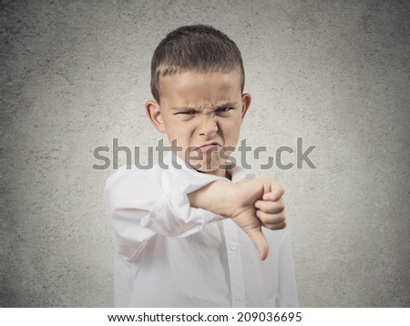 Portrait unhappy, Angry, Displeased Child giving Thumbs Down hand gesture, isolated grey wall background. Negative human Face Expressions, Emotions, Feelings, attitude, life perception, body language  - stock photo