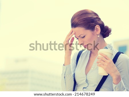 Portrait unhappy young business woman stressed bothered by mistake having bad headache holding cup coffee isolated standing outside corporate office. Negative human emotion expression feeling reaction - stock photo