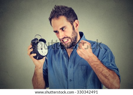 Portrait upset angry young man screaming at alarm clock isolated on gray wall background. Employee running late. Time management concept   - stock photo