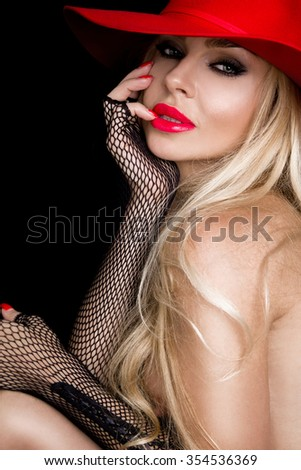 Portrait Very beautiful young blond sexy female model in erotic black gloves, red hat  carnival  in a sexy makeup and red mouth on a black background and coquettishly holding fingers on lips