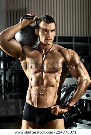 portrait very brawny athletic guy - bodybuilder,   with  weight, in gym - stock photo