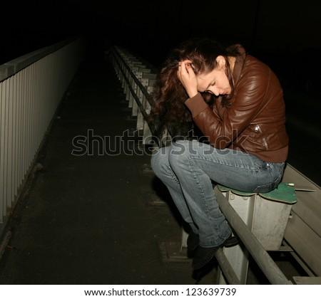 portrait very sad girl on metal Bridge on highway - stock photo