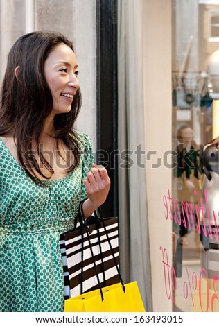 Portrait view of a young and attractive Japanese woman looking at the display window of an exclusive store in sales in the city of London while on holiday, holding carrier bags and smiling.