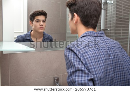 Portrait view of a young teenager man looking at himself in a home bathroom mirror, getting ready for school in the morning, home interior. Health and well being, male care and grooming, indoors.