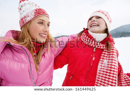 Portrait view of two joyful young women friends having fun and laughing while on a skiing holiday in a white snow  landspace scenery in the mountains, laughing with big expressions, outdoors. - stock photo