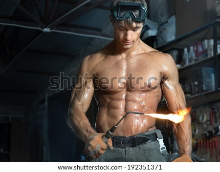 Portrait with naked torso of young athletic guy with gas torch on dark background. Fitness concept - stock photo