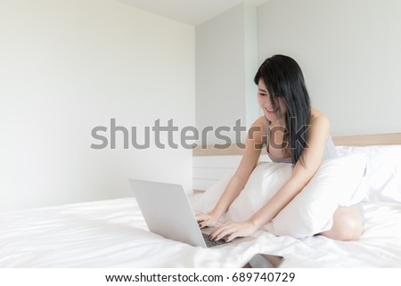 portrait woman model using laptop on bed white at bedroom  home to soft sport focus