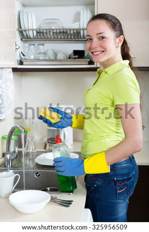 Portrait woman washing plates in home kitchen - stock photo
