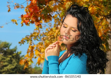 Portrait woman with beauty make up in autumn leaves outdoors - stock photo