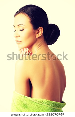 Portrait woman wrapped in towel touching chin. - stock photo