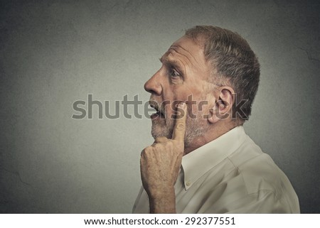 Portrait worried man thinking looking up isolated on grey wall background with copy space. Human face expressions, emotions, feelings, body language, perception
