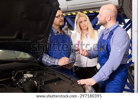 Portrait worried young woman and specialists at auto repair shop. Focus on the left man - stock photo