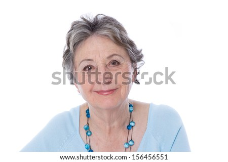 Portrait: Wrinkled face of an older attractive and smiling older woman. Isolated over white wearing blue pullover and jewelry. - stock photo