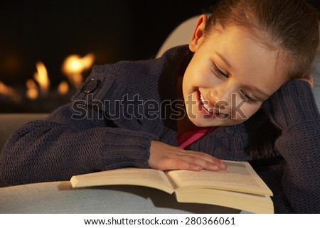 Portrait 7 year old girl reading by firelight - stock photo