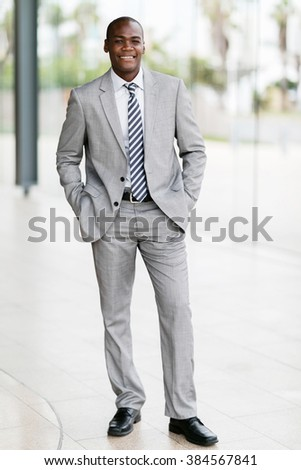 portrait young afro american businessman standing in office - stock photo