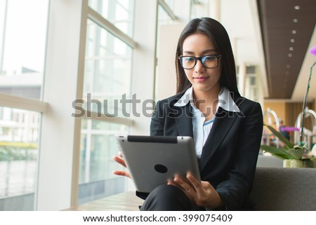 Portrait young attractive businesswoman working with digital tablet.