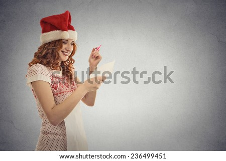 Portrait young attractive girl santa helper in red hat holding reading christmas wish list isolated grey wall background with copy space. Holiday season celebration tradition concept. Positive emotion - stock photo