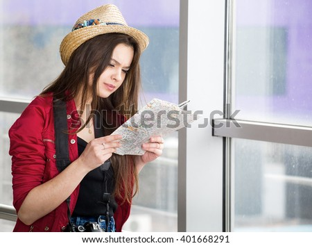 portrait, young attractive woman in a red coat and hat standing in the terminal or at the station with a suitcase and looking at the map. The girl met on a trip. - stock photo