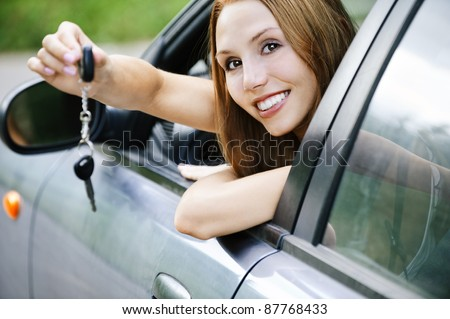 portrait young attractive woman sitting salon automobile looking out open window stretched out hand keys car - stock photo