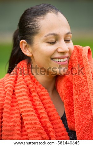Portrait young beautiful  active fit woman wiping sweat of smiling face with towel after exercising outdoor, closed eyes, blurred background.