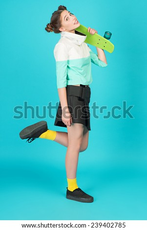 Portrait young beautiful crazy girl posing on a blue background in the studio with Longboard wearing a fashionable outfit, smiling - stock photo