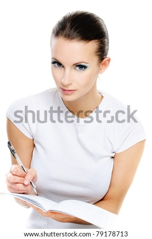 Portrait young beautiful dark-haired woman-student who writes in exercise book with pen, isolated on white background. - stock photo