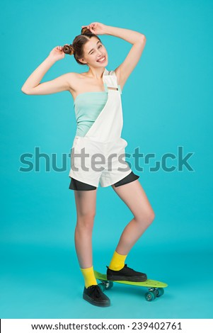 Portrait young beautiful sensual crazy girl posing on a blue background in the studio with Longboard wearing a fashionable outfit, smiling, concept of youth and sports - stock photo