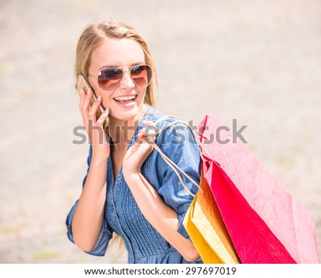Portrait young blond hair woman with shopping bags talking on the phone and smiling at camera. - stock photo
