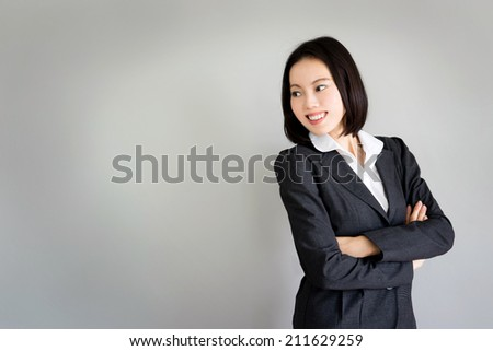 Portrait young business woman standing against grey background - stock photo