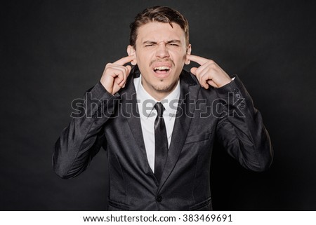 portrait young businessman in black suit covering his ears with his hand. emotions, facial expressions, feelings, body language, signs. image on a black studio background. - stock photo