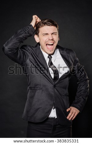 portrait young businessman in black suit scratching his headgesture. emotions, facial expressions, feelings, body language, signs. image on a black studio background. - stock photo