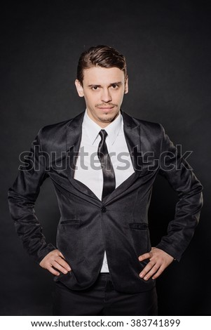 portrait young businessman in black suit with hands on his waist and smirking. emotions, facial expressions, feelings, body language, signs. image on a black studio background. - stock photo