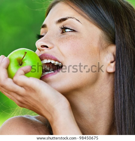 portrait young charming brunette woman biting green apple background summer park - stock photo