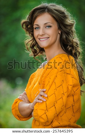 portrait young charming woman long-haired curly smiles background summer green forest - stock photo