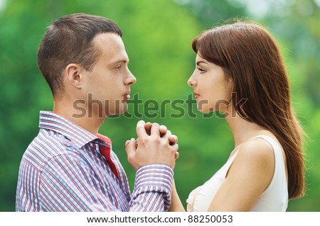 portrait young couple loving facing each other hold hands background summer green park - stock photo