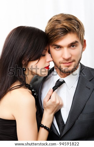 Portrait young couple, woman hold grab man tie with closed eyes, wear evening dress and suit, glamour vogue style, guy sensual looking at camera, sitting indoors - stock photo