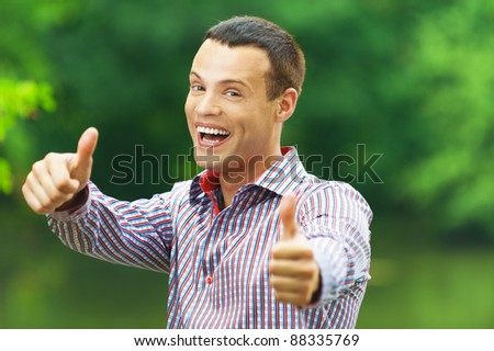 portrait young cute funny guy background green park shows thumb - stock photo