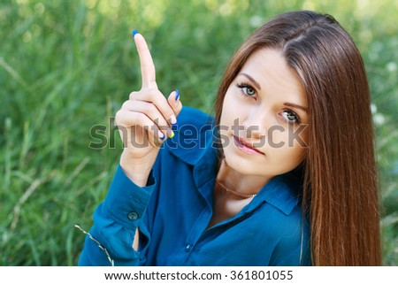 portrait young cute long-haired women point to copyspace background summer green park - stock photo