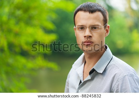 Portrait young dark-haired man glasses serious background summer green park