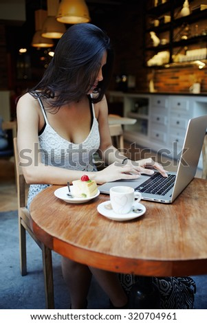 Portrait young elegant sexy woman with gorgeous breasts breakfast in luxurious coffee shop and work on laptop computer, female freelancer sit at the table with net-book, cup of coffee and tasty cake  - stock photo