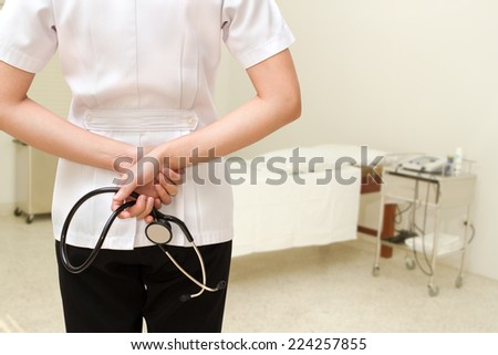 Portrait young female doctor holding a stethoscope standing in the hospital - stock photo