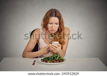 portrait young girl eating green salad looking at phone seeing bad news or photos annoyed  confused disappointed face expression isolated on grey wall background  - stock photo