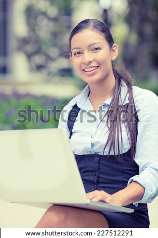 Portrait young happy business woman resting hands on computer laptop keyboard looking at camera isolated outside park with trees background. Positive face expression emotion. Technology concept