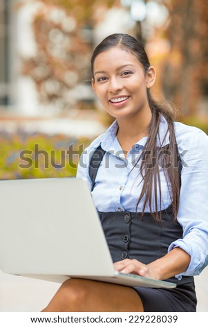 Portrait young happy business woman working on computer laptop looking at camera isolated outside park with autumn trees background. Positive face expression emotion. Wireless technology concept