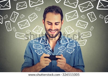 Portrait young happy man busy sending messages emails from smart phone email icons coming out flying of mobile phone isolated on gray wall background. Telecommunications, internet, data plan concept - stock photo