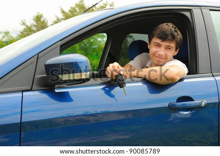 portrait young happy man showing the keys sitting in new car - stock photo